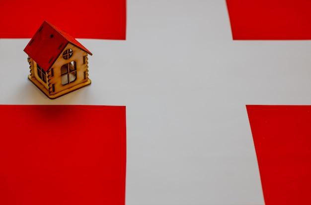 Bienes raíces en suiza casa de madera en la bandera suiza. concepto de propiedad, alquiler o hipoteca.