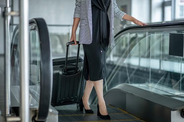 Bienestar. mujer en vestido negro con tacones con maleta con ruedas subiendo escaleras mecánicas al aeropuerto, sin rostro