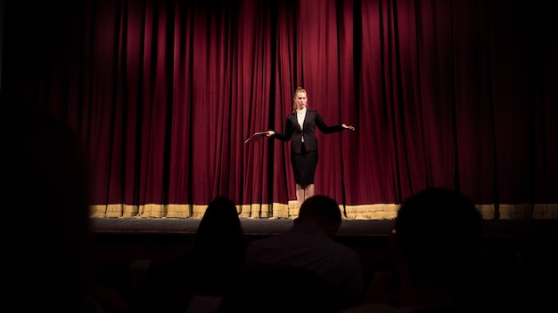Bienvenida alegre. oradora femenina dando presentación en el salón del taller. centro de negocios. vista trasera de los participantes en audiencia. evento de conferencia, formación. educación, reunión, concepto de negocio.