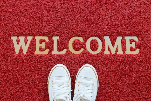 Bienvenido alfombra con zapatillas blancas en él.