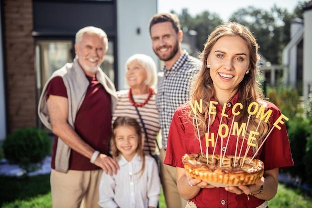 Bienvenido a casa. familia alegre de pie