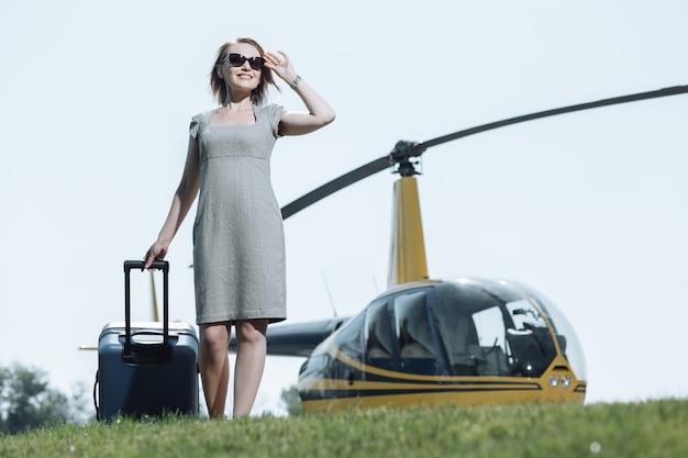 Bienvenido a casa. hermosa joven llegando a un helipuerto y cargando su equipaje mientras sonríe felizmente, después de haber regresado de un viaje de negocios