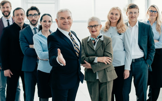 Bienvenido empresario de pie delante de un equipo de grandes empresas