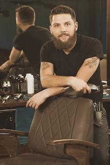 Bienvenido a mi barbería. guapo barbero profesional barbudo sonriendo a la cámara recostada en una silla