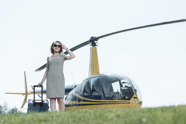 Bienvenido de nuevo. mujer joven optimista que lleva su maleta a través del helipuerto y sonriendo, habiendo regresado a casa después del vuelo en helicóptero