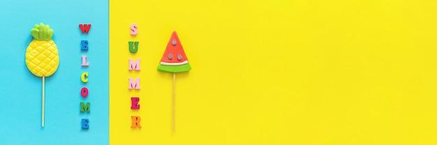 Bienvenido verano colorido texto, piña y sandía piruletas en palo sobre fondo amarillo azul. vacaciones conceptuales