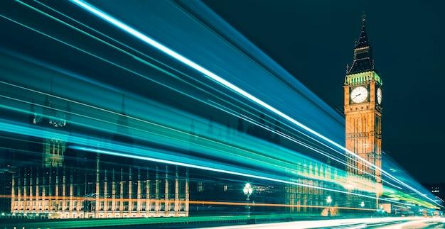 Big ben, uno de los símbolos más destacados tanto de londres como de inglaterra, como se muestra de noche junto con las luces de los coches que pasan