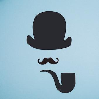 Bigote ornamental cerca de tubo de papel y sombrero de copa