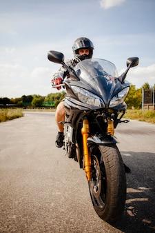 Biker cabalgando sobre la moto negra