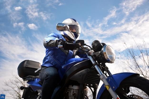 Biker con casco azul pasando por una carretera.