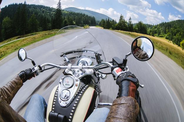 Biker hombre montando su moto en la carretera