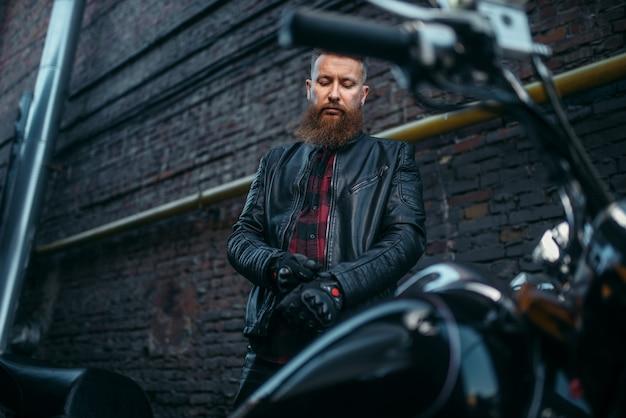 Biker masculino en chaqueta de cuero se pone guantes