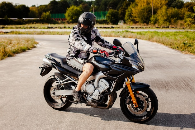 Biker en la moto estacionada en la carretera