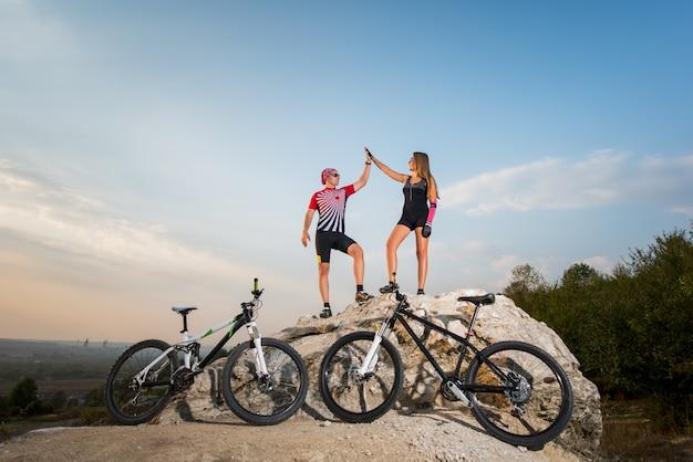 Biker pareja de pie sobre una roca cerca de bicicletas y dando choca esos cinco contra el cielo azul