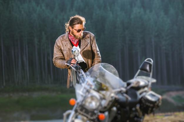 Biker está sentado en su moto de viaje de larga distancia con bosque en el fondo