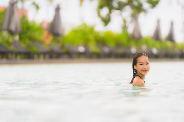 Bikini asiático hermoso joven del desgaste de la mujer del retrato alrededor de piscina en playa del océano del océano del centro turístico del hotel casi