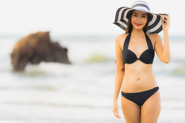 Bikini asiático joven hermoso del desgaste de mujer del retrato en el océano del mar de la playa