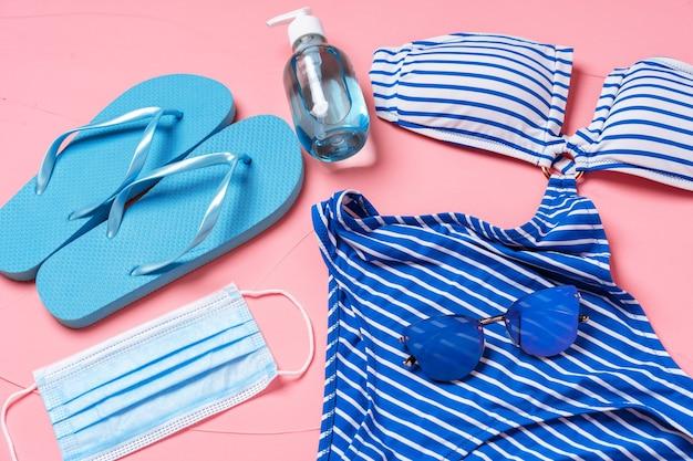 Bikini azul, chanclas con mascarilla protectora y desinfectante de manos sobre fondo rosa.