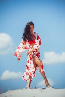 Bikini sexy cuerpo mujer sintiéndose libre con estómago delgado y muslos lisos vistiendo colorida bufanda de moda falda traje de baño ropa de playa mostrando la pérdida de peso. concepto de bienestar de spa de belleza láser.
