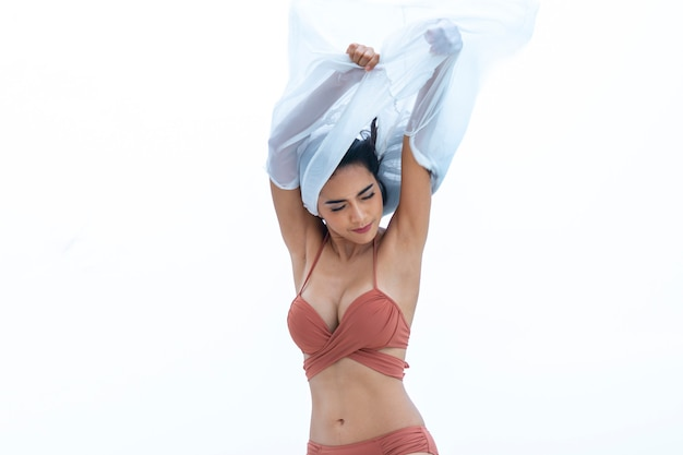 Bikini sexy mujer sosteniendo tela blanca camisa flotante tela de pie