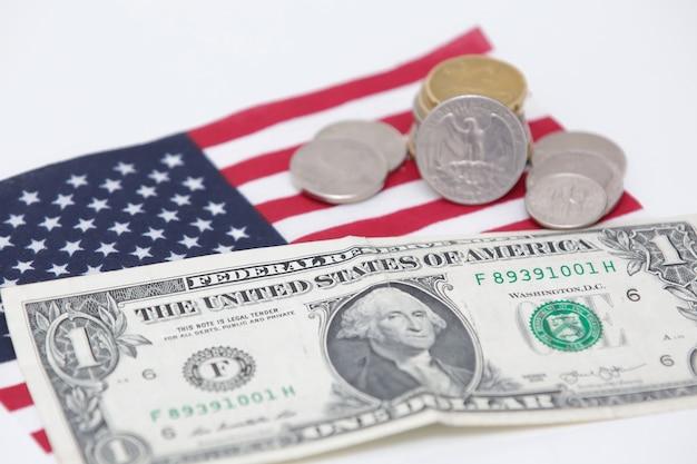 Billete de 1 dólar de los estados unidos con monedas y bandera en la parte inferior
