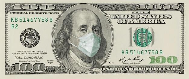 Billete de 100 dólares con una máscara facial de benjamin franklin del coronavirus covid-19 en los estados unidos.