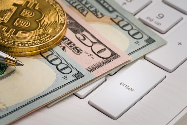 Billete de banco de los eeuu del primer con la moneda y pluma en el teclado