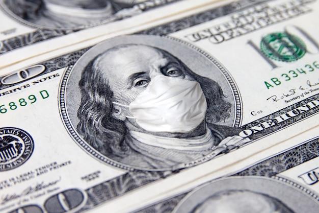 Billete de dinero de cien dólares. benjamin franklin con mascarilla médica facial.