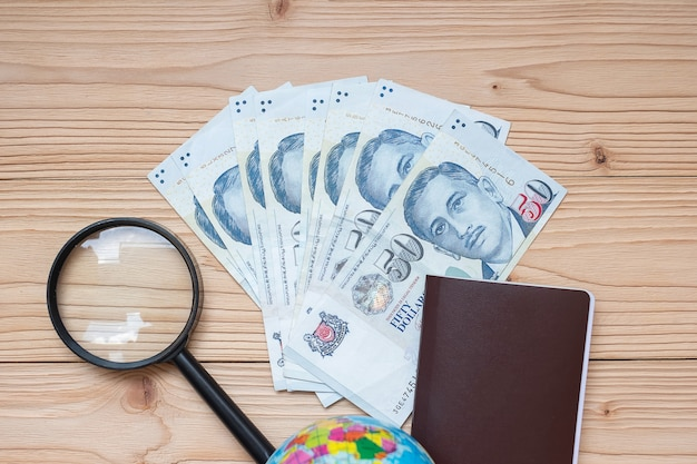 Billete de dinero con pasaporte, lupa, globo en mesa de madera
