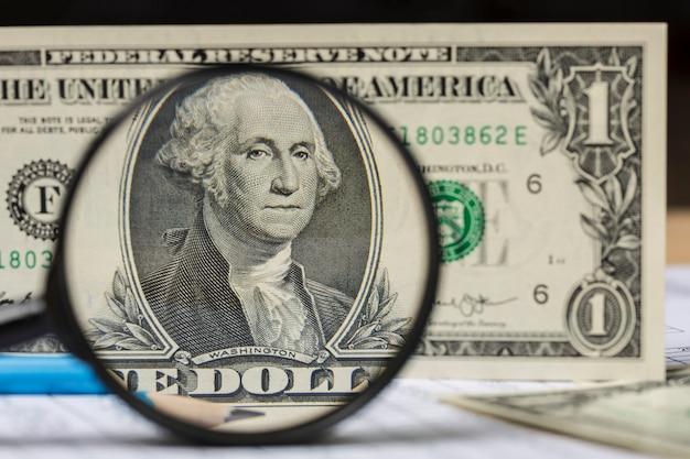 Billete de un dólar americano y lápiz a través de una lupa