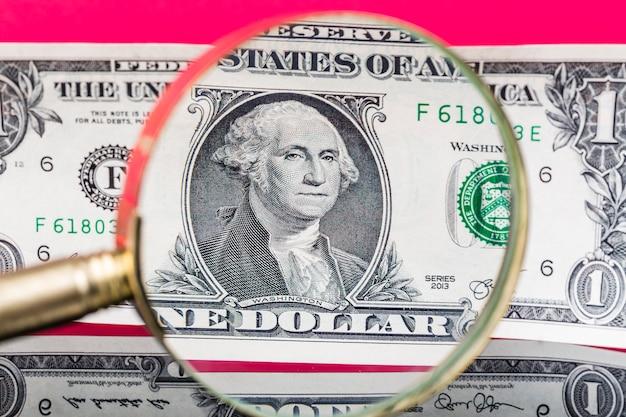 Billete de dólar americano a través de una lupa sobre fondo rojo agradable