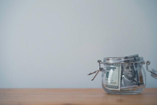 Billete de dólar dentro del tarro de ahorro guarro en la mesa de madera y copie el espacio. ahorro de dólares por concepto de inversión.