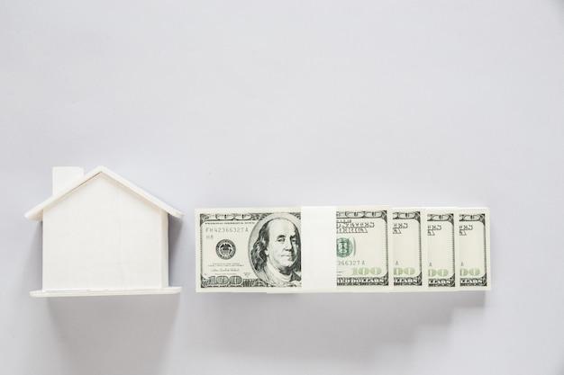 Billete de dólar de vista superior con casa de madera, concepto de finanzas