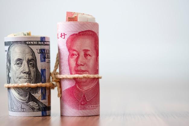 Billete de dólar y yuan en mesa de madera