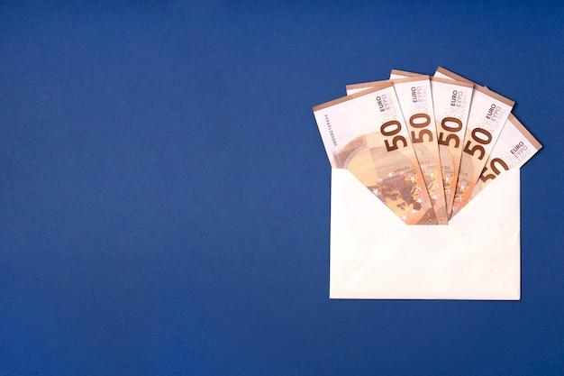 Billete en euros en el sobre sobre fondo azul. ahorro de dinero, regalo, concepto de entrega en efectivo.