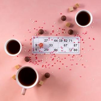 Billete de lotería con barril de madera número 14 y tazas de té de café, dulces dulces de chocolate sobre fondo de corazones de color rosa. día de san valentín 14 de febrero concepto mínimo. formato cuadrado