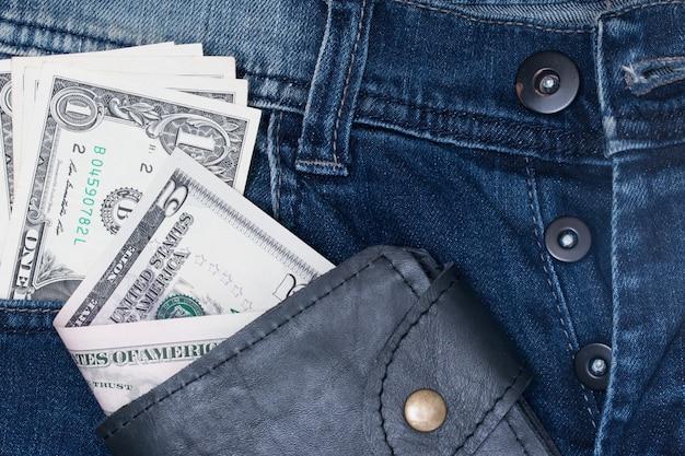 Billetera de cuero y dólar con bolsillo de jeans.
