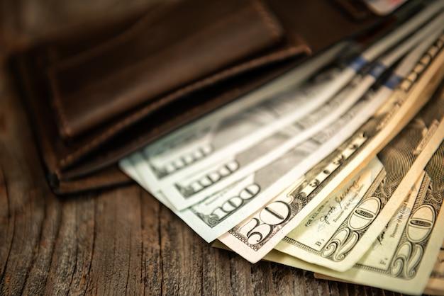 Billetera de cuero marrón con dólares sobre una superficie de madera vieja
