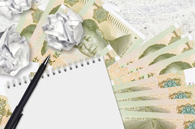 Billetes de 1 yuan chino y bolas de papel arrugado con bloc de notas en blanco. malas ideas o menos concepto de inspiración. buscando ideas para inversión