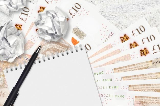 Billetes de 10 libras esterlinas y bolas de papel arrugado con bloc de notas en blanco. malas ideas o menos concepto de inspiración. buscando ideas para inversión