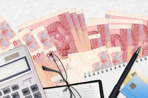 Billetes de 100 baht tailandés y calculadora con gafas y bolígrafo. concepto de pago de impuestos o soluciones de inversión. planificación financiera o papeleo contable