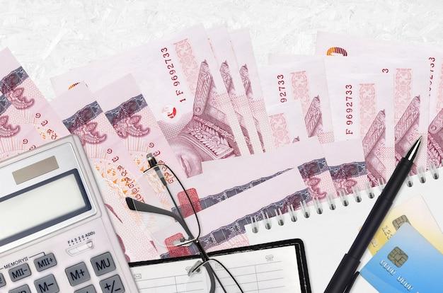 Billetes de 100 baht tailandés y calculadora con gafas y bolígrafo. concepto de temporada de pago de impuestos o soluciones de inversión. planificación financiera o papeleo contable