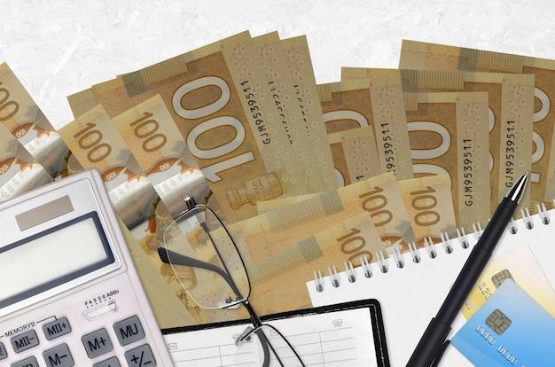 Billetes de 100 dólares canadienses y calculadora con gafas y bolígrafo. concepto de temporada de pago de impuestos o soluciones de inversión. planificación financiera o papeleo contable