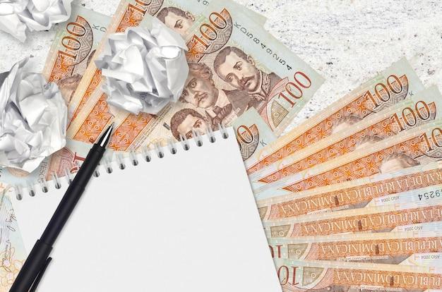 Billetes de 100 pesos dominicanos y bolas de papel arrugado con bloc de notas en blanco. malas ideas o menos concepto de inspiración. buscando ideas para inversión