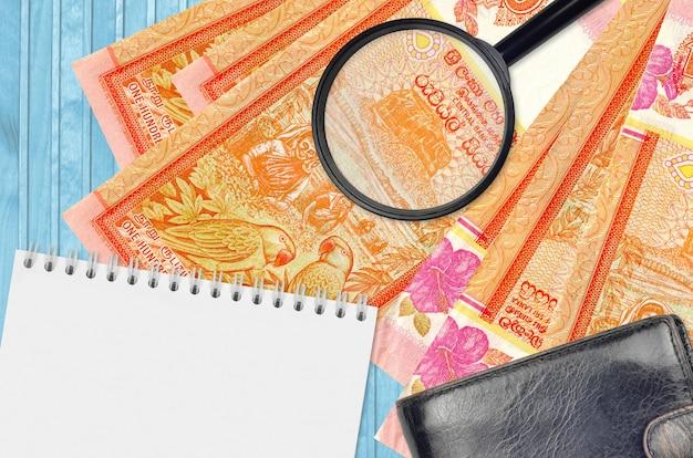 Billetes de 100 rupias de sri lanka y lupa con monedero negro y bloc de notas