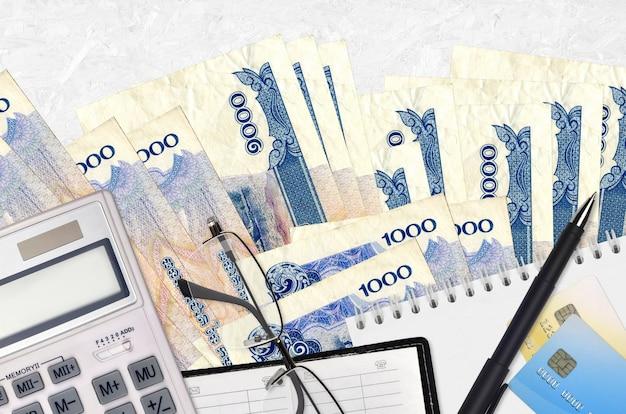 Billetes de 1000 riels camboyanos y calculadora con gafas y bolígrafo