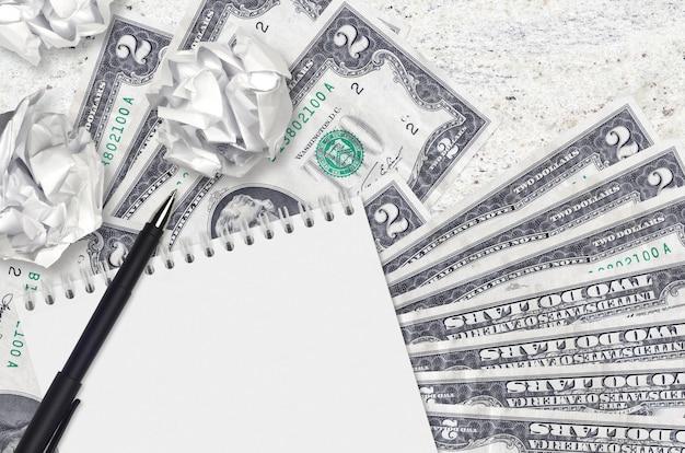 Billetes de 2 dólares estadounidenses y bolas de papel arrugado con bloc de notas en blanco. malas ideas o menos concepto de inspiración. buscando ideas para inversión
