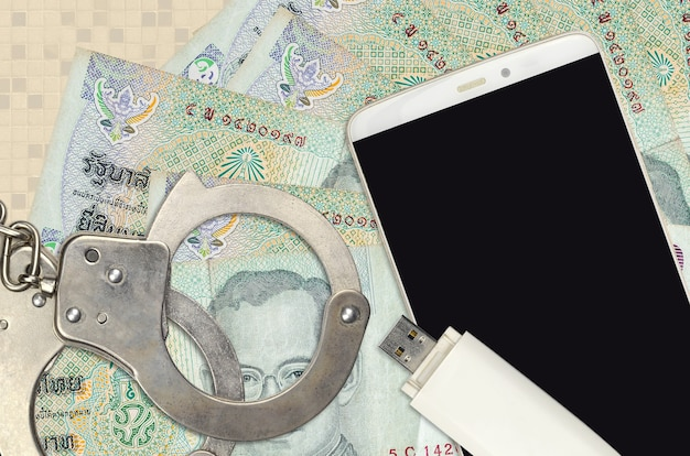 Billetes de 20 baht tailandés y smartphone con esposas de policía. concepto de ataques de phishing de piratas informáticos, estafa ilegal o distribución suave de software espía en línea
