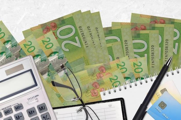Billetes de 20 dólares canadienses y calculadora con gafas y bolígrafo. concepto de temporada de pago de impuestos o soluciones de inversión. planificación financiera o papeleo contable