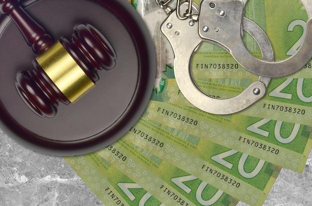 Billetes de 20 dólares canadienses y martillo de juez con esposas de policía en el escritorio de la corte. concepto de juicio judicial o cohecho. elusión o evasión fiscal